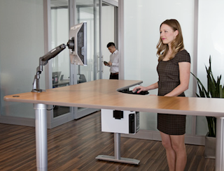 woman standing at a sit-to-stand desk